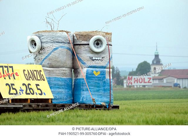 16 May 2019, Saxony, Liebschützberg: Minions figures made of straw bales, car wheels and other decorative material stand on a field on the Bundesstraße 6...