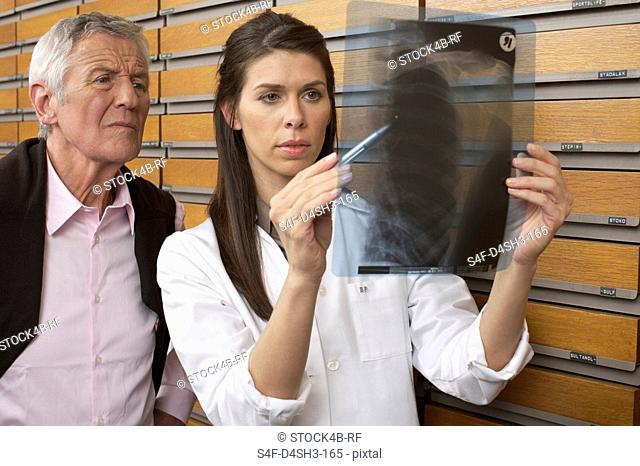 Female pharmacist watching old man's x-ray