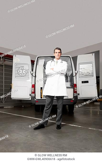 Doctor standing with an ambulance behind him
