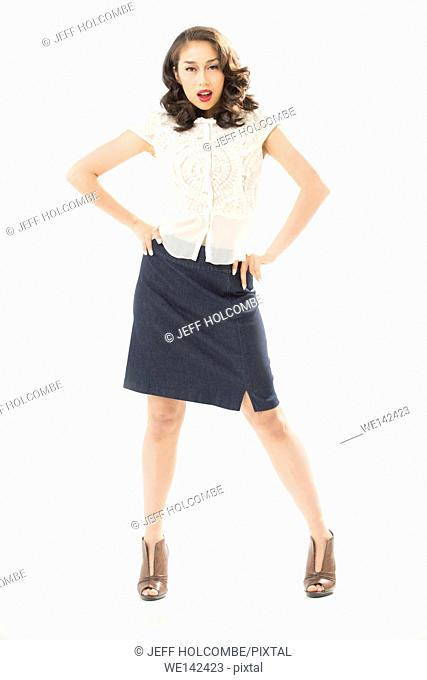 Beautiful young woman in white blouse and blue denim skirt, full length in brown heels, hands on hips, facing forward confidently