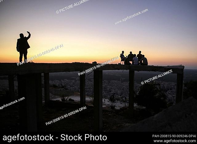 14 August 2020, Syria, Arihah: A man takes a selfies with the skyline while a group of young men gather on top of a building for drinks and hookah smoking after...