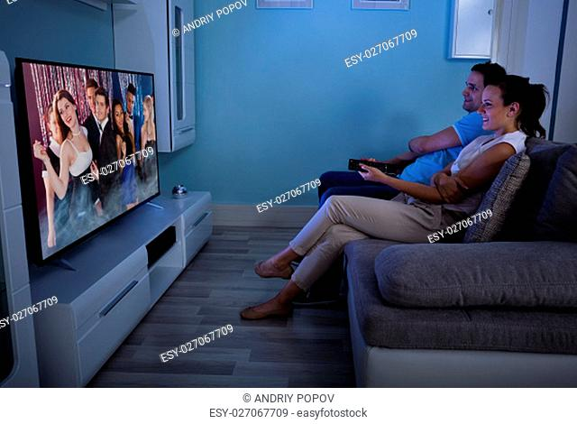 Happy Couple Watching Film On Television Together In Living Room At Home