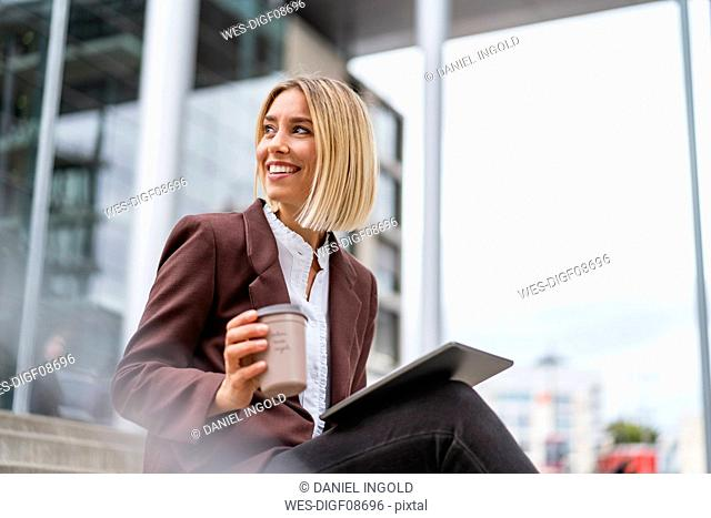 Smiling young businesswoman with tablet and coffee to go in the city