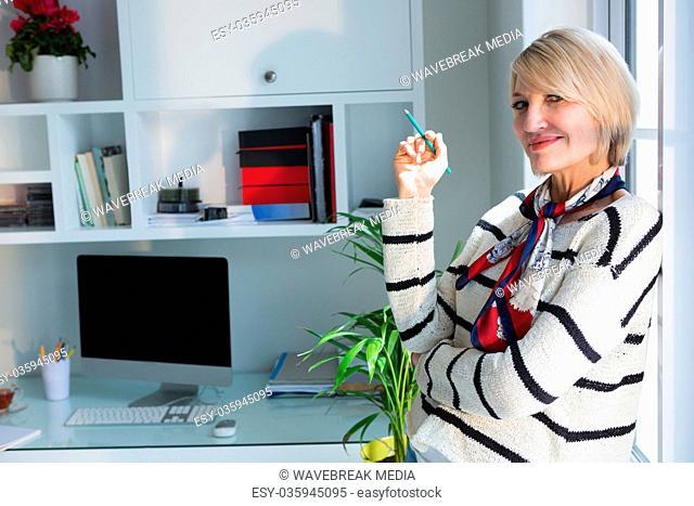 Confident woman holding pencil