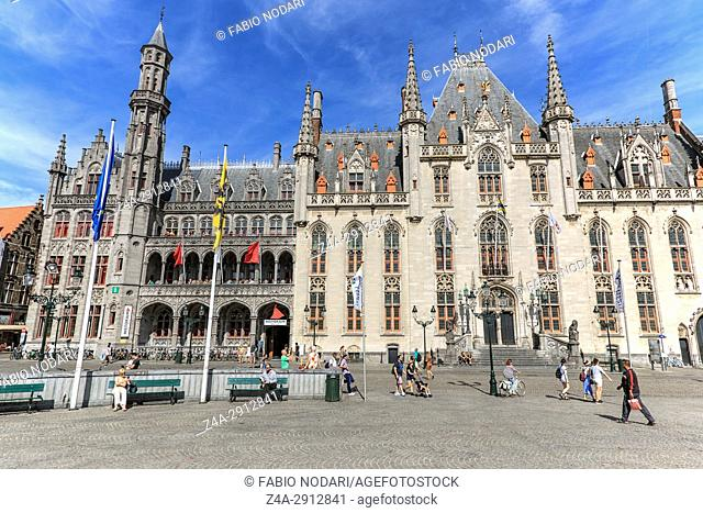 Bruges, Belgium - July 7, 2017: Tourists walking in front of the Provinciaal Hof in the market square in the center of Bruges