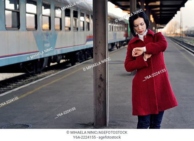 Mid adult looking at her wristwatch at the train station