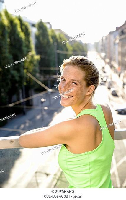 Young female runner taking a break on city footbridge