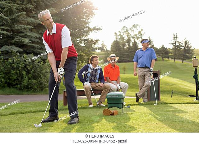 foursome of golfers with one golfer on the tee-box