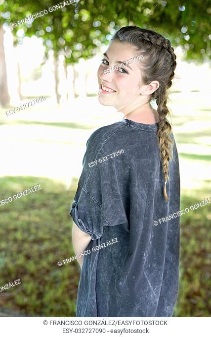 Girl in gray dress smiling in gardens of the University of Alicante, Spain