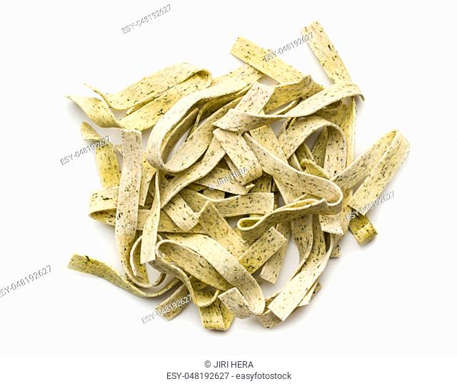 Raw italian pasta. Dry noodles with spinach isolated on white background