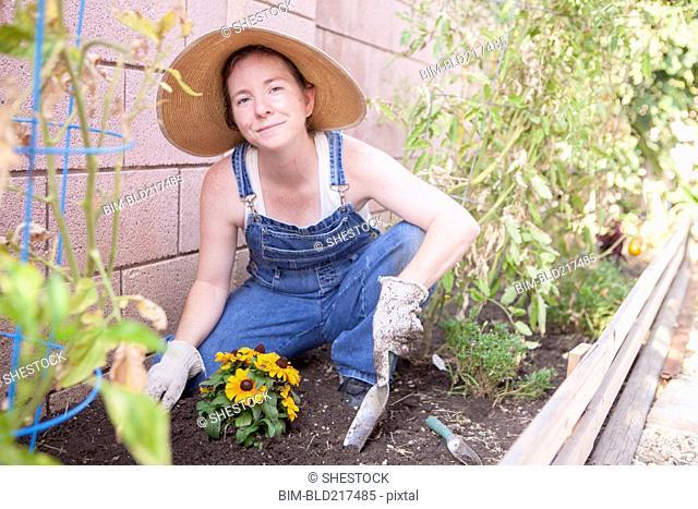 Mixed race farmer planting flowers in garden