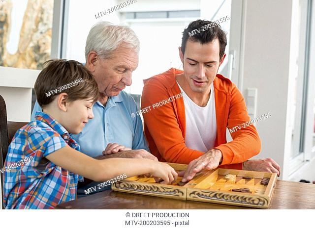 Grandfather, father and son playing backgammon