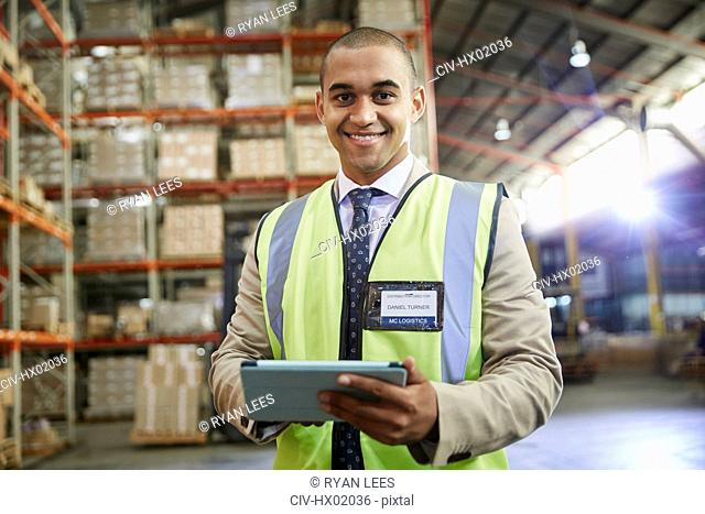 Portrait confident manager with digital tablet in distribution warehouse