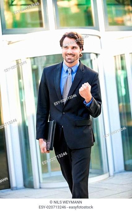 Attraktiver junger geschäftsmann jubelnd vor einem Geschäftsgebäude