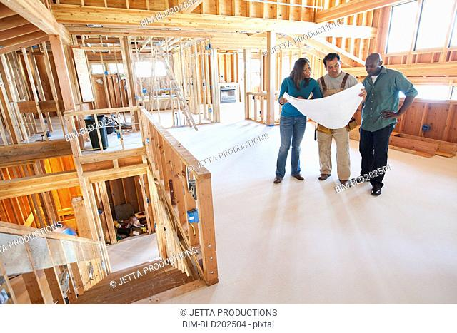 Black couple and construction worker looking at blueprints in unfinished room