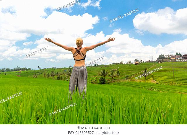 Relaxed woman, arms rised, enjoying life of beautiful green rice fields on Bali. Young lady feeling free, relaxed and happy