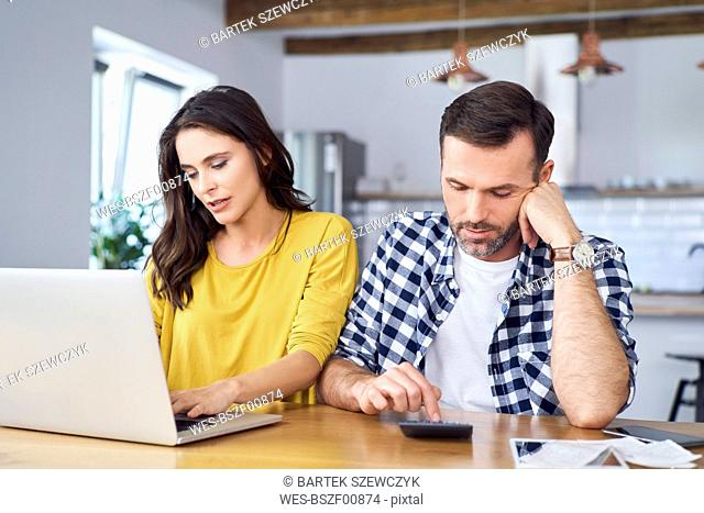 Worried couple sitting at dining table, using laptop, checking finances