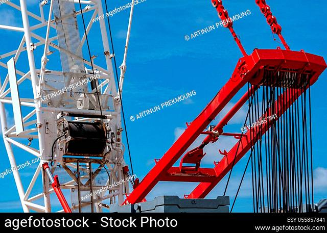 Closeup crawler crane with wire rope sling on crane reel against blue sky. Lifter equipment in construction site. Crawler crane for rent service