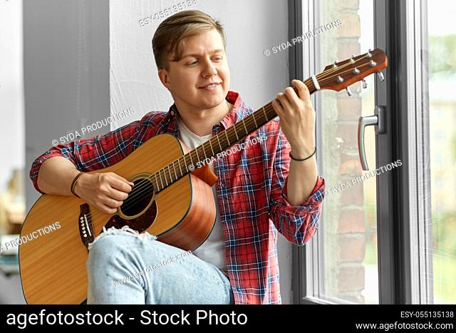 young man playing guitar sitting on windowsill