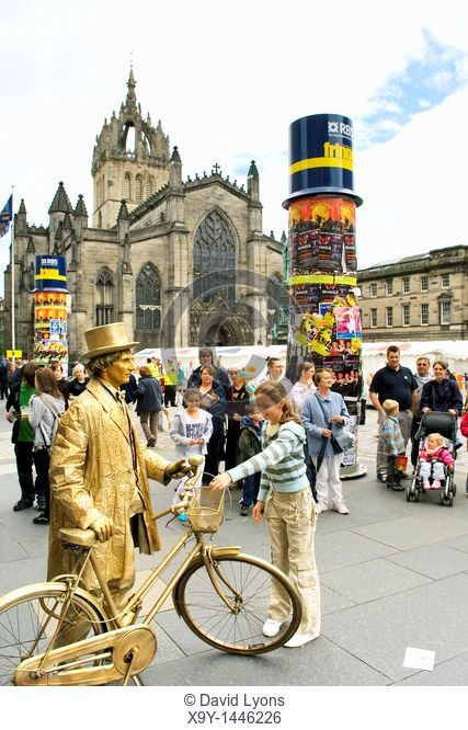 Edinburgh Festival Fringe, Scotland  Gold living statue entertains in front of St  Giles Cathedral on the High Street