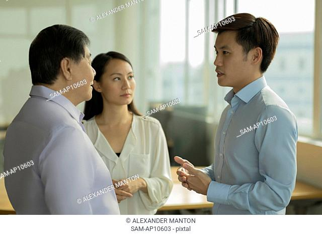 Singapore, Three people talking in office