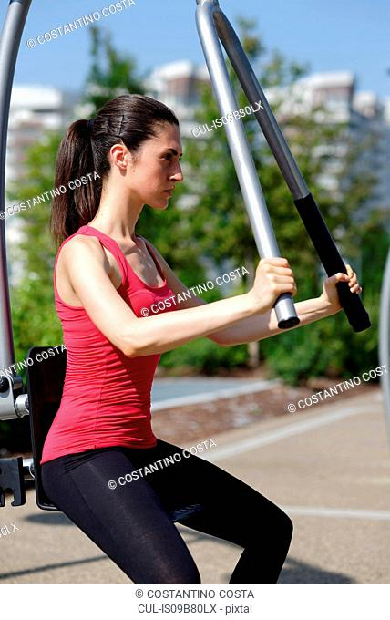 Young woman exercising in urban gym