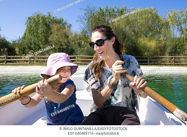 Four years old blonde girl with hat with woman mother sitting in boat, smiling happy, paddling at park lake