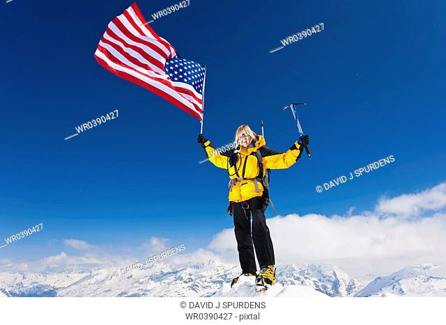 Mountaineer celebrates on summit flying the stars and stripes