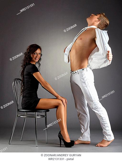 Striptease dance. Tanned girl and sexy male dancer