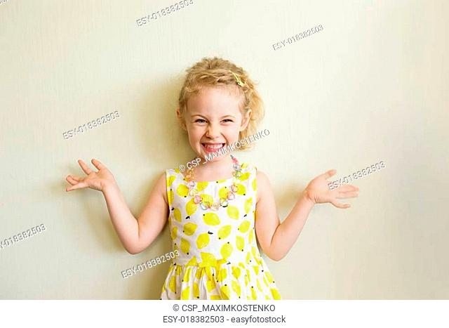 Portrait of emotional little girl in summer dress at home