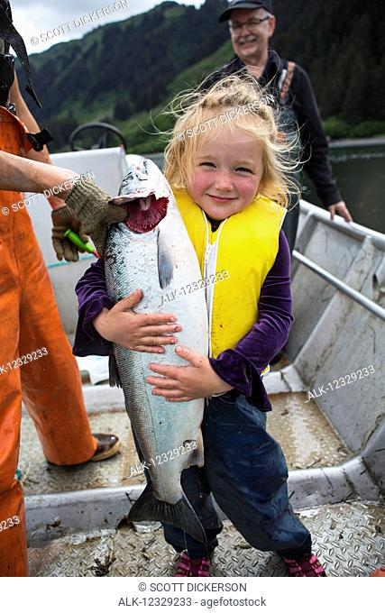 Young girl holding a salmon in a set-net skiff, South-central Alaska; Seldovia, Alaska, United States of America