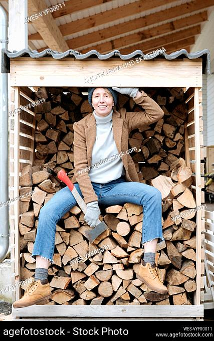 Portrait of smiling mature woman with axe sitting on firewood