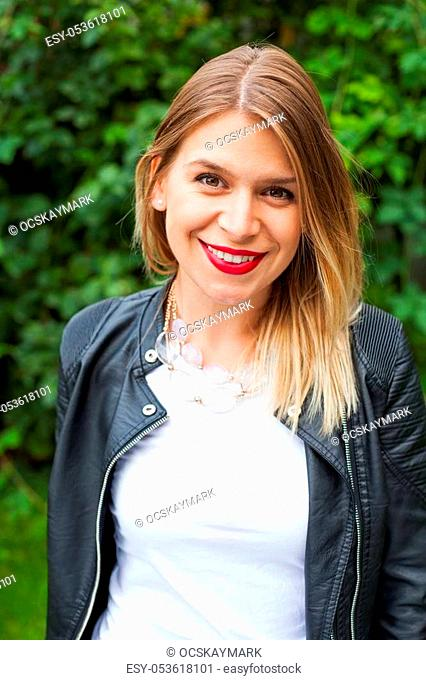 Charming young lady wearing a leather jacket, smiling at the camera outdoor