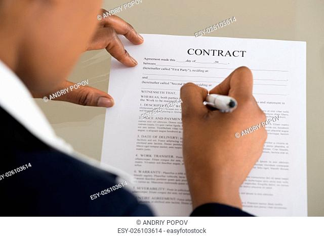 Close-up Of A Businesswoman Filling Contract Form