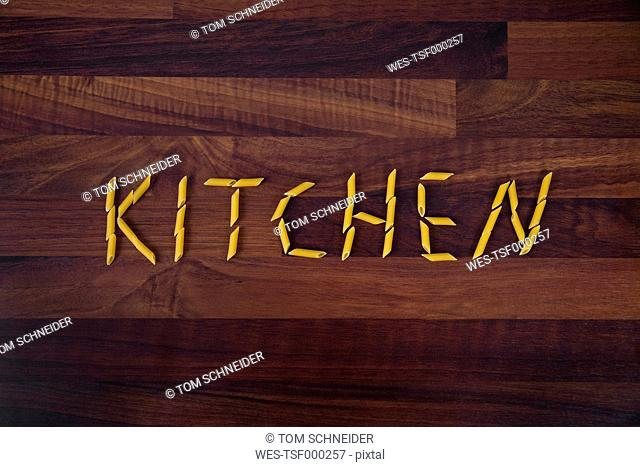 Close up of word kitchen written with penne on wooden background