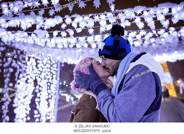 Happy young couple kissing in winter decoration