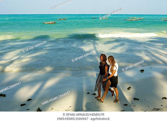 Tanzania, Zanzibar, Jambiani, youngs women walking on a sandy beach