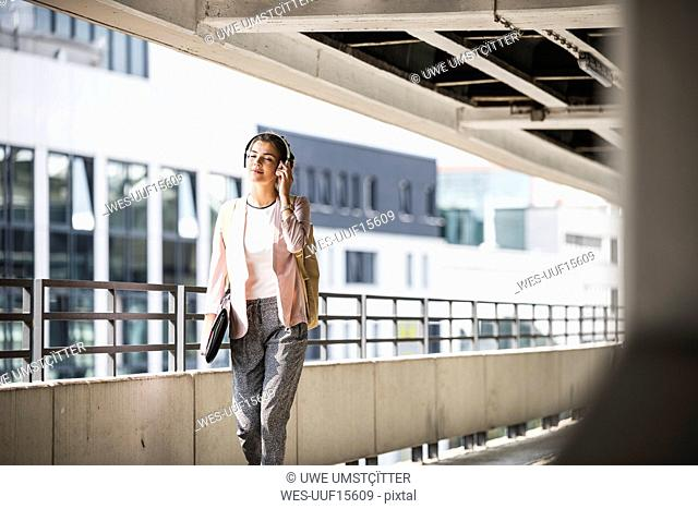 Young businesswoman walking in parking garage, listeing music with her headphones