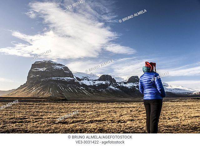 Young woman enyoying Lómagnúpur view, a cliffs that towers over Björninn Mountain, west of the Núpsvötn Lakes in Skeiðarársandur (region of Suðurland, Iceland)