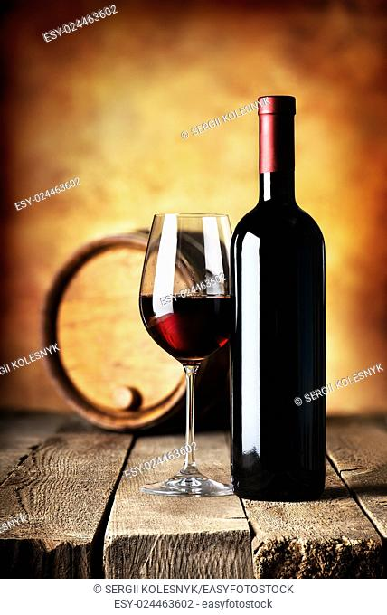Red wine in bottle and cask on a wooden table