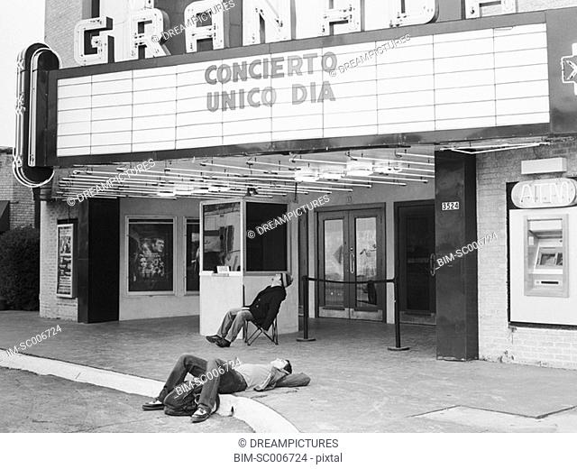 Man laying on ground in front of movie theater
