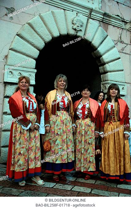 National costume women before the gate of the Old Town of Kotor in the internal bay of Kotor in Montenegro in the Balkans at the Mediterranean Sea in Europe
