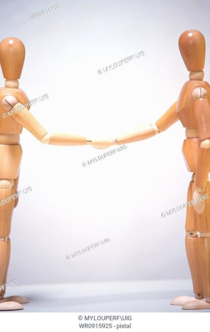 Two mannequins shaking hands