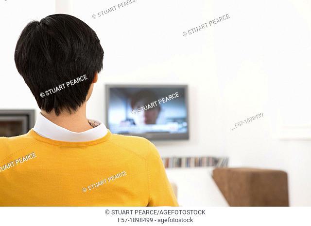 Young Asian man watching TV
