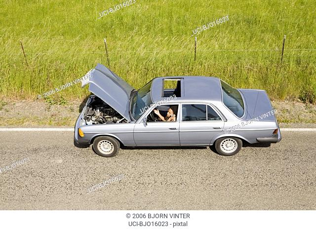 Woman in broken down car