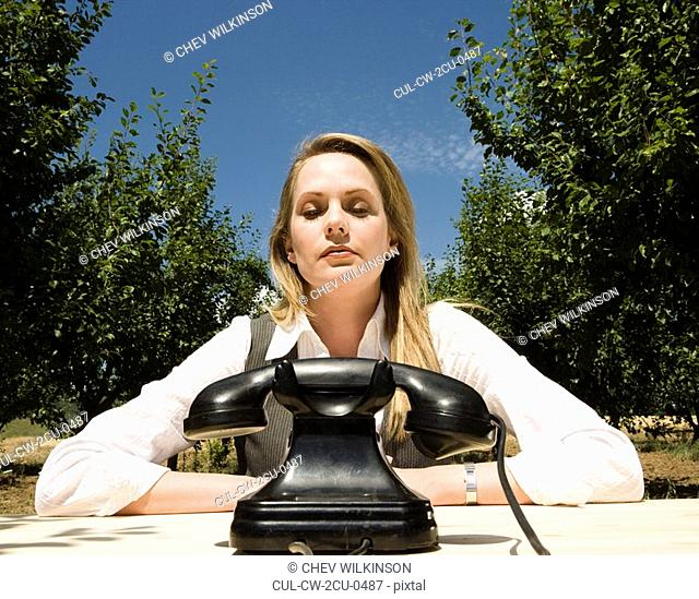 Woman sitting at desk with old telephone in orchard