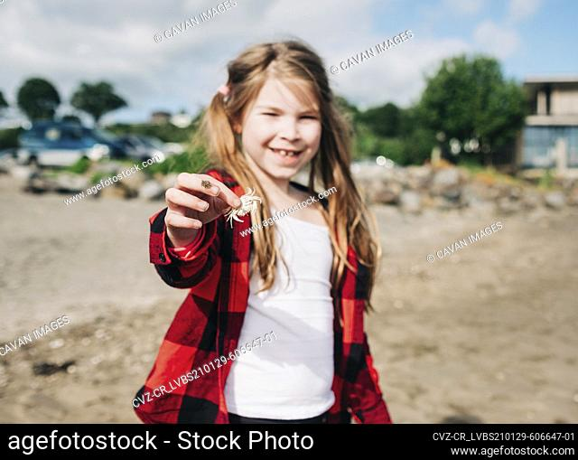 Young girl holding small dead crab on the beach