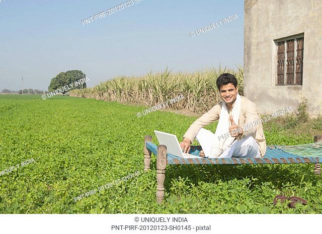 Farmer using a laptop in the field, Sonipat, Haryana, India