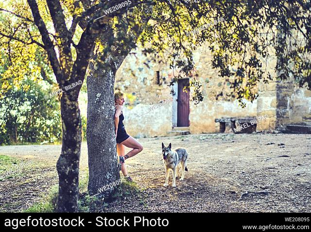 Portrait of a young mature caucasian woman standing outdoor with a wolf dog in a mediterranean rural area with trees an a house summertime