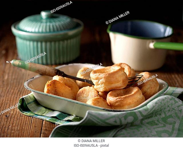 Dish of roast potatoes and yorkshire puddings with vintage props on wood